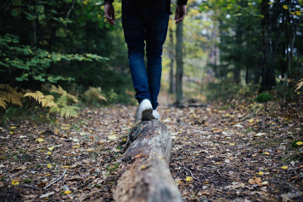 ihminen kävelee metsässä tukilla kuvituskuva
