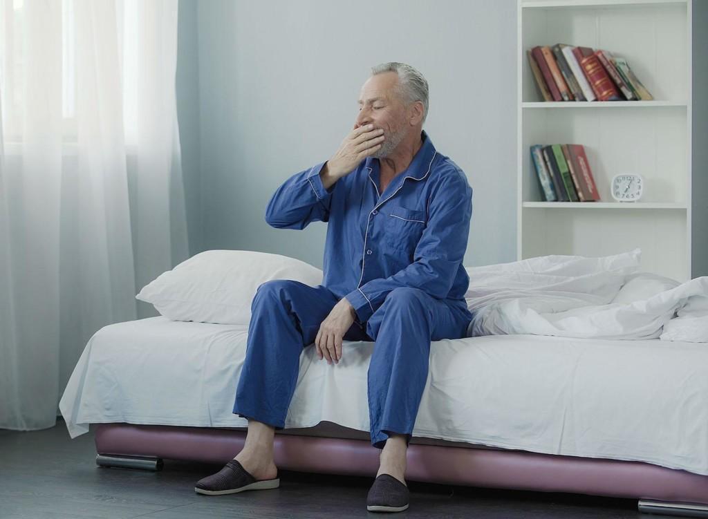 Valokuva miehestä, joka haukottelee sängynlaidalla.